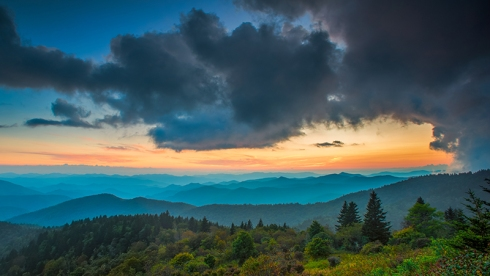 The light over the Appalachian Mountains along the Blue Ridge Parkway in Western North Carolina paints the sky with the setting sun.